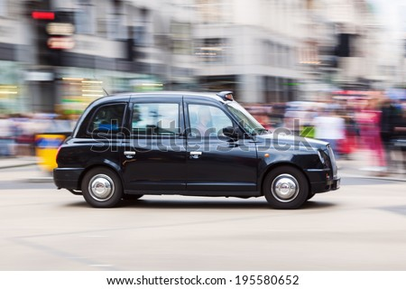 LONDON - MAY 20: traditional London Taxi in motion blur on May 20, 2014 in London. The black London Taxis are one of the world famous symbols of London. - stock photo
