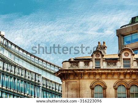 London modern architecture next to old architecture featuring modern glass building and old victorian houses - stock photo