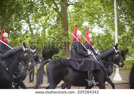 LONDON - NOV 6: Marching the Queen's Guards during traditional Changing of the Guards ceremony at Buckingham Palace on November 6, 2013 in London, United Kingdom. - stock photo