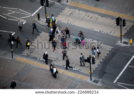 LONDON - OCT 27: People cross pedestrian crossing in London on October 27, 2014. There were 132 fatalities on London's roads in 2013, with fatalities involving pedestrians down 6% from 2012. - stock photo