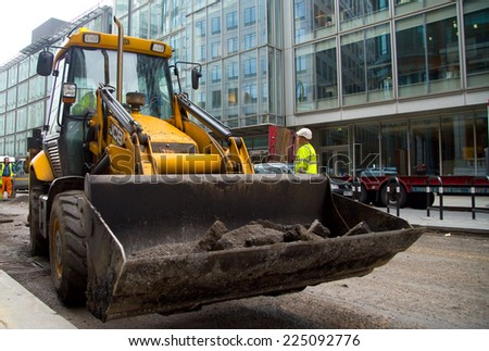 LONDON - OCTOBER 18TH: Unidentified workman operates a JCB on October 18th, 2014 in London, England, UK. JCB is one of the world's top manufacturers of construction equipment. - stock photo