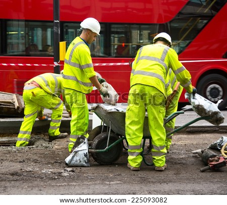 LONDON - OCTOBER 18TH: Unidentified workman preparing a mixture on October 18th, 2014 in London, England, UK. The UK construction industry contributes  £83 billion a year to the economy. - stock photo