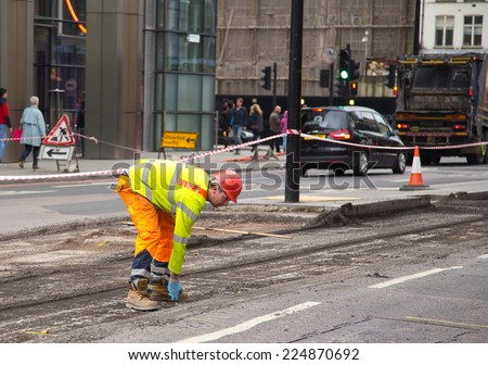 LONDON - OCTOBER 18TH: Unidentified workman resurfacing a road on October 18th, 2014 in London, England, UK. The city council carry's out annual road condition surveys - stock photo