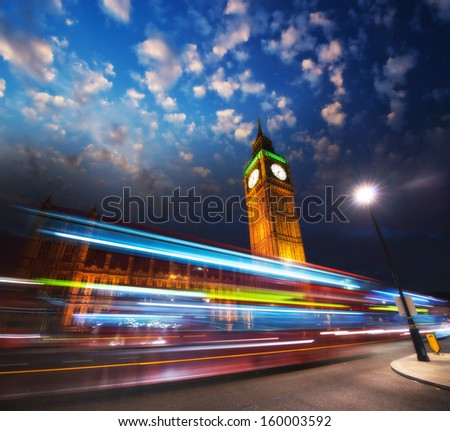 London. Red Bus light trails under famous Big Ben Tower at sunset.