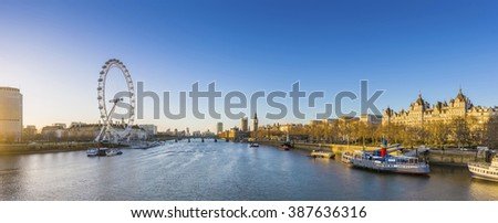 London's skyline view at sunrise with famous landmarks, Big Ben, Houses of Parliament and ships on River Thames with clear blue sky - London, UK - stock photo