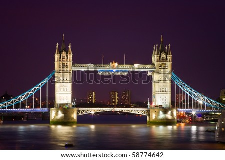 London's Tower Bridge illuminated at night time and reflections in water