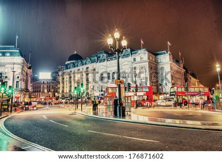 LONDON - SEP 30, 2013: People stroll in Piccadilly at night. From pubs to upmarket bars, nightclubs and late night shopping, Piccadilly is a popular nightlife area - stock photo