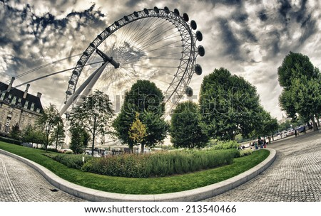 LONDON - SEP 29, 2013: Tourists visit London Eye Wheel. The entire structure is 135 metres (443 ft) tall and the wheel has a diameter of 120 metres (394 ft). - stock photo