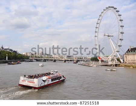 LONDON – SEPTEMBER 24: A City Cruises tour boat sails on the Thames River on September 24, 2011 in London, England.  Thames is the longest river in England with 346 km long. - stock photo