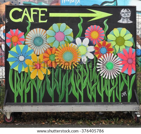 LONDON - SEPTEMBER 19, 2015. Portable directional cafe sign in the Nomadic Community Gardens at Shoreditch in the Borough of Tower Hamlets in east London, UK. - stock photo