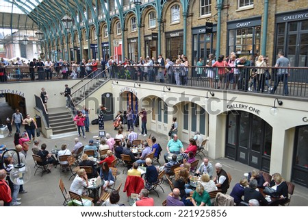London - September 13: tourists at a cafe watching musicians in the old market of Covent Garden, London, UK on September 13, 2014.