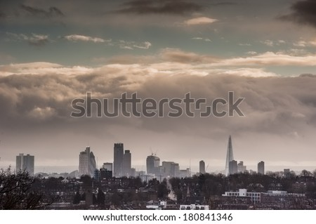 London skyline under dramatic dark clouds - stock photo