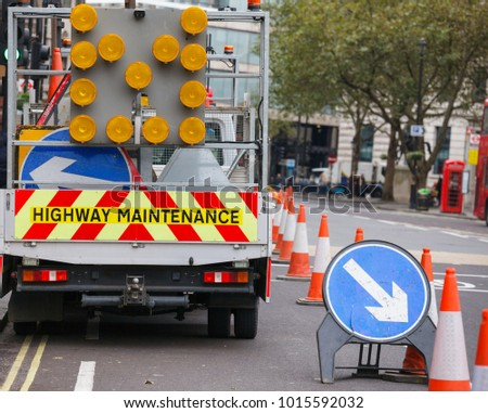 London street barricaded with Highway Maintenance vehicle and traffic cones with Keep Right diversion traffic sign - roadworks concept