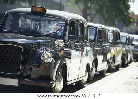 London Taxis Lined Up On Sidewalk - stock photo