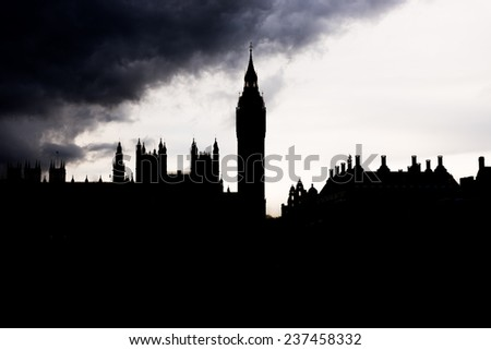 London - The Houses of Parliament and the Big Ben silhouetted under thick dark clouds - stock photo