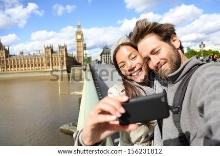 London tourist couple taking photo near Big Ben. Sightseeing woman and man having fun using smartphone camera smiling happy near Palace of Westminster, Westminster Bridge, London, England. - stock photo
