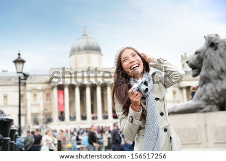 London tourist woman on Trafalgar Square in front of National Gallery taking photo holding camera smiling happy laughing having fun. Beautiful girl on travel vacation, London, England, United Kingdom. - stock photo