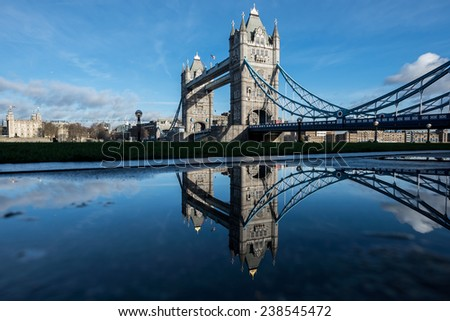 London - Tower Bridge is reflected in a rain puddle near City Hall on a beautiful sunny day.  - stock photo