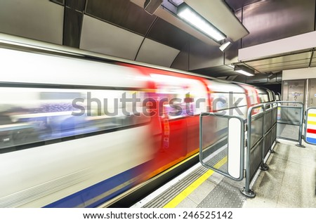 London tube arriving in a station. - stock photo