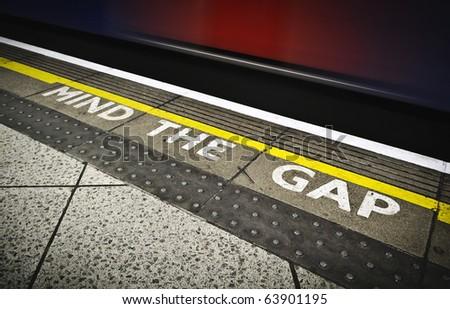 London tube platform edge. Painted warning on the floor. - stock photo