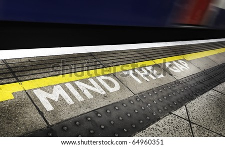 London tube platform edge. Painted warning on the floor. Train passing by. - stock photo