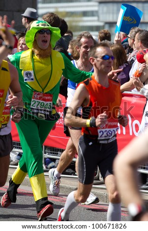 LONDON, UK - APR. 22: A man dresses in fancy dress as tens of thousands of people pass Tower Bridge during the London Marathon on the Apr 22, 2012 in London, UK - stock photo