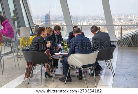 LONDON, UK - APRIL 22, 2015: Business meeting in public sky garden of Walkie-Talkie building - stock photo