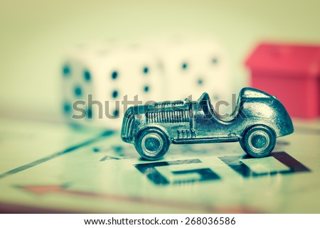 LONDON,UK - APRIL 1,2015 : Car token and dice on a vintage monopoly game board - stock photo