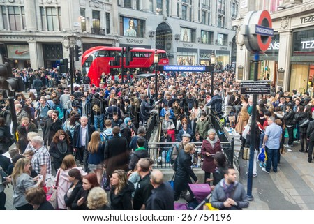 LONDON, UK - APRIL 08, 2015: Crowded Oxford Circus Station entrance due to severe delays in the tube Central Line. Lots of commuters and tourists waiting on the street to enter the station. - stock photo