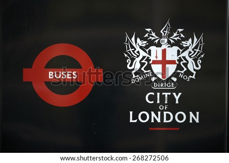 LONDON, UK - APRIL 06: Detail of black City of London banner in bus stop featuring its coat of arms next to the Transport for London red logo. April 06, 2015 in London.  - stock photo