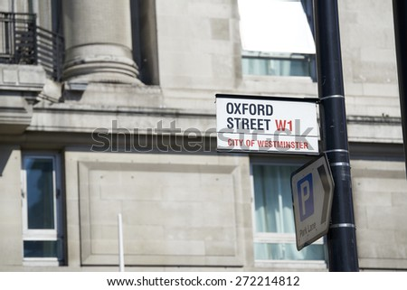 LONDON, UK - APRIL 22: Detail of Oxford Street sign next to a parking direction arrow on pole. April 22, 2015 in London. Oxford Street is the main commercial street in the city. - stock photo
