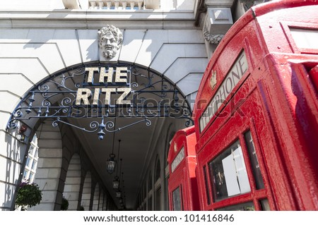 LONDON, UK - APRIL 30: Details of the Ritz hotel entrance, with red phone booth. April 30, 2012 in London. The luxury hotel dates back from 1905. - stock photo