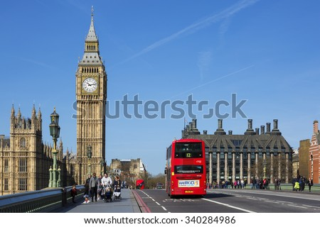 LONDON, UK - APRIL 12, 2015: double-decker bus passes pedestrians walking in front of Big Ben and Houses of Parliament on Westminster Bridge. - stock photo