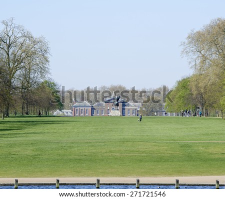 LONDON, UK - APRIL 22: Kensington Palace seen from the Serpentine lake on a sunny spring day, with George Frederic Watts's equine sculpture Physical Energy in the frame. April 22, 2015 in London.  - stock photo