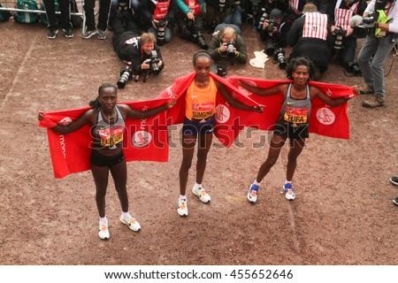 London, UK - 24 April 2016. Kenyan runners Florence Kiplagat,  Jemima Sumgong (winner) and Tigist Tufa (Ethiopia) pose for photos after crossing te finish line of the Virgin Money London Marathon. - stock photo