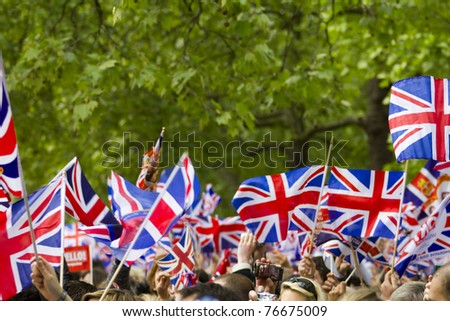 LONDON, UK - APRIL 29: Many people wave flags at Prince William and Kate Middleton wedding on  April 29, 2011 in London, United Kingdom - stock photo