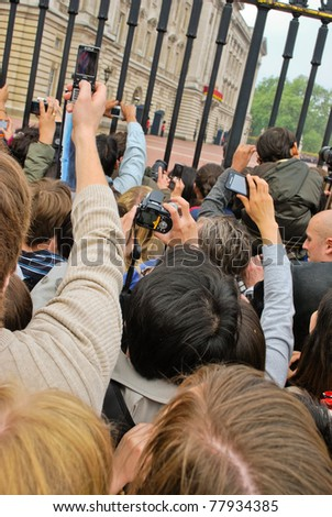 LONDON, UK - APRIL 29: People taking pictures of the first public kiss of Prince William and Kate Middleton at their wedding, April 29, 2011 in front of Buckingham Palace in London, United Kingdom - stock photo