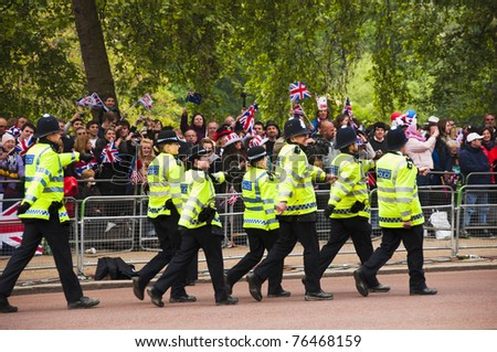 LONDON, UK - APRIL 29: Policemen walking on the Mall at Prince William and Kate Middleton wedding, April 29, 2011 in London, United Kingdom - stock photo