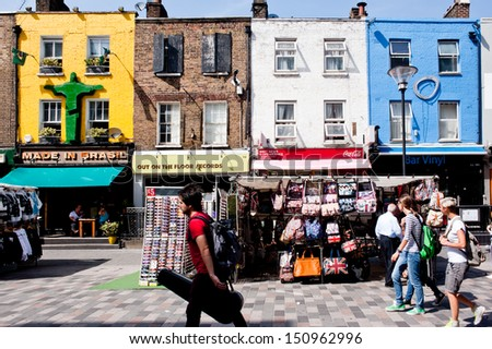 LONDON, UK - AUG 21: people and stalls in Inverness St Market in Camden, London on August 21, 2013.Once a fresh produce market, it is now manly tourist oriented, selling souvenirs, crafts and clothing - stock photo