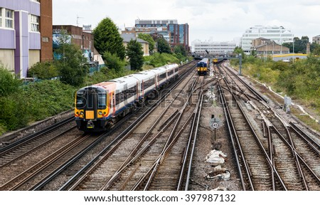 London, UK.  31 August 2014.  A South West Trains commuter service heads towards the centre of the city.  Increasing rail fares are of growing concern in the UK.  - stock photo