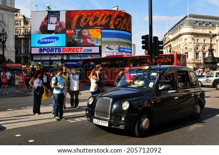 LONDON, UK - AUGUST 9, 2012: Tourists walk in Piccadilly Circus, major commercial area of London, home of important landmarks and shops. - stock photo