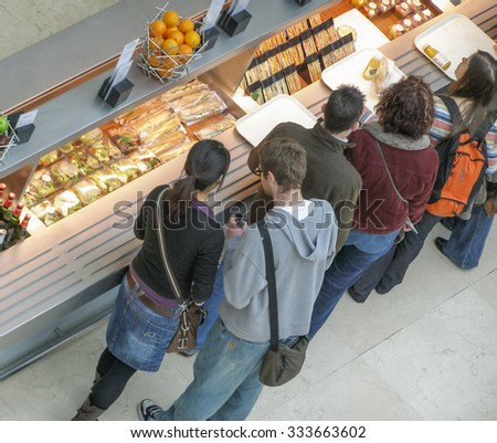 LONDON, UK - CIRCA MARCH, 2008: People queueing at the British Museum cafeteria bar in the Great Court - stock photo