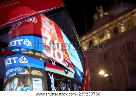 LONDON, UK - DECEMBER 19: Detail of London red bus line 38 reflecting lights of Piccadilly Circus at night. December 19, 2014 in London. - stock photo