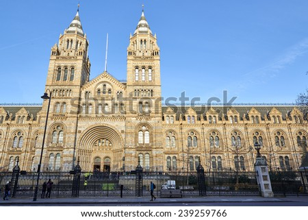 LONDON, UK - DECEMBER 20: Facade of the Natural History museum in bright sunny day with people walking past. December 20, 2014 in London.