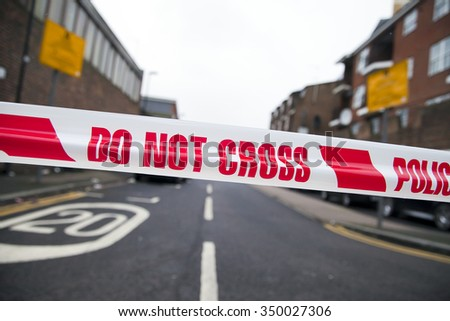 LONDON, UK - DECEMBER 11, 2015  Police tape in Bracknell Road, Wood Green in North London after a man was shot dead during a police investigation. - stock photo