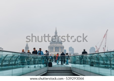 LONDON, UK - December 6, 2016: Unidentified people on Millennium Bridge. St Paul's Cathedral seen from Millennium Bridge in London.