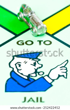 LONDON,UK - FEBRUARY 11, 2015 : Car token next to the GO TO JAIL space in a Monopoly game board - stock photo