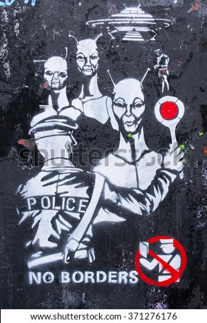 "London, UK - January 24 2016: Graffiti showing a policeman stopping aliens with words ""No borders"" written below it. It refers to the current migration crisis and Europe's increased intolerance."