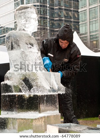 LONDON, UK - JANUARY 15: Ice Sculptor Carve a Figure at the Annual London Ice Sculpture Festival, with Office Blocks in the Background. Canary Wharf, London. January, 15 2010