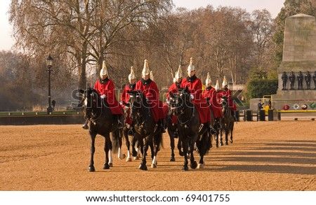 LONDON, UK- JANUARY 19: Members of the Queen's Royal Horse Guards, the Royal Life Guard Regiment, riding to the Changing of the Guard Ceremony in Horse Guards Parade. January 19, 2011 in London, UK. - stock photo